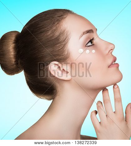Beautiful model applying cosmetic cream dots on her face over blue background