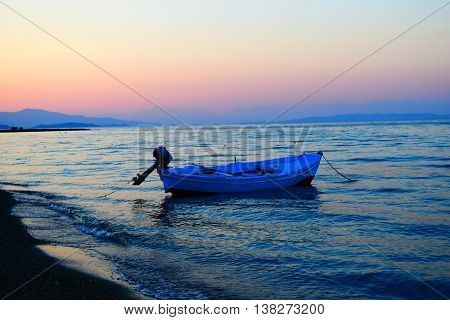 Blue boat in Messonghi at colourful sunset in Corfu, Greece.