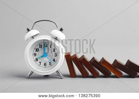 Alarm clock blocked dominoes row on grey background