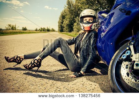Beautiful biker woman sitting by her motorcycle on a highway. The spirit of freedom and independence.