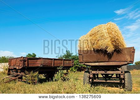 Bales of hay on a trailer standing in a green field under a blue sky.