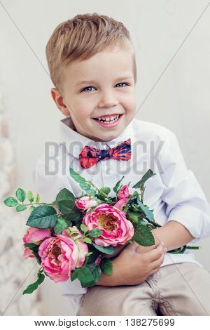 happy little boy with a bouquet of roses on a white background