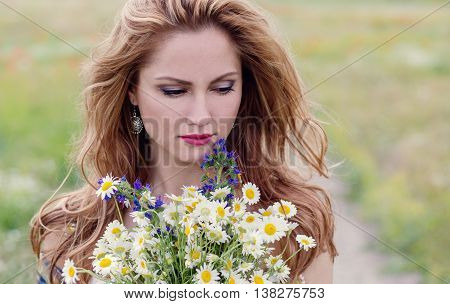 young woman with a bouquet of field daisies spring