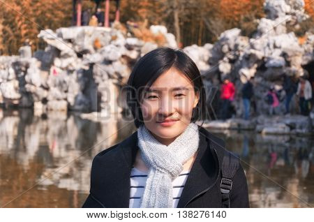 A chinese woman smiling wearing a scarf and winter coat within a traditional chinese garden standing near water in Shanghai China.