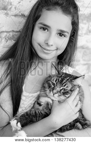 pretty girl teenager 10-11 years holding a cat in the room ( black and white )