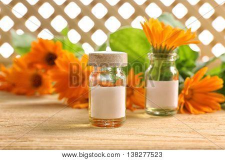 Healing calendula flower in small glass bottle on light wooden background