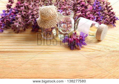Healing meadow sage flower in small glass bottle on light wooden background
