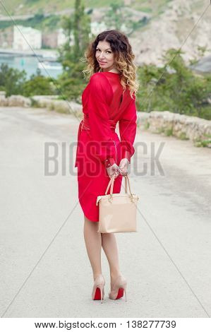 young woman in a red dress posing on a background of the bay