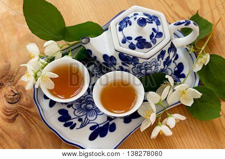 Jasmine green tea in cups and ceramic teapot on a tray. Green tea and jasmine flowers.