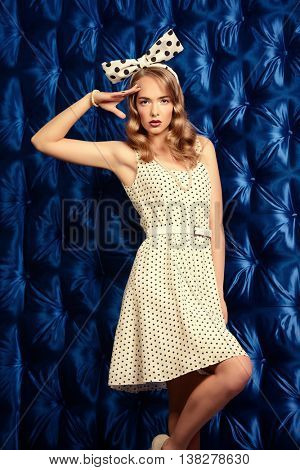 Pretty pin-up girl wearing white polka-dot dress and an elegant bow on her head. Beauty, fashion. Pin-up style.