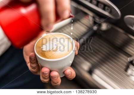 Closeup of barista pouring milk into art cappuccino