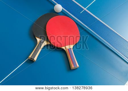 Ping Pong Rackets And Table Tennis Net On Wooden Table