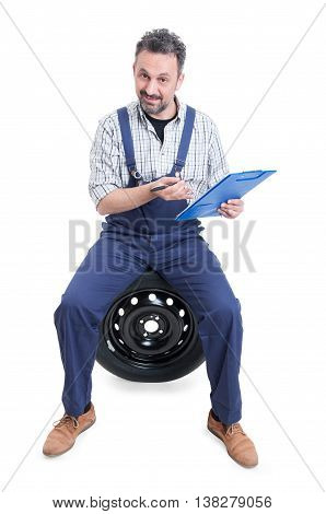 Handsome Mechanic Sitting On Tire And Holding Clipboard
