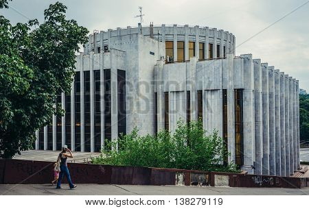 Kiev Ukraine - July 26 2015. Woman with child walks near building of International Convention Center in Kiev