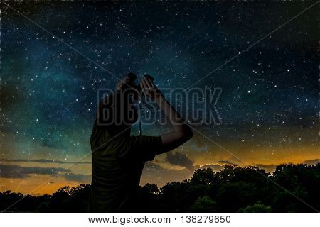 Silhouette of man is observing night sky.