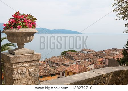 Mediterranean Flowerpot On A Post, View To Garda Lake Over The Roofs