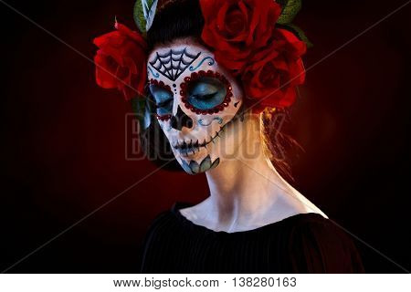 Female portrait in mexican santa muerte mask eyes closed.