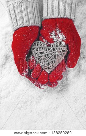 Hands in warm red gloves holding wicker heart on snowy background