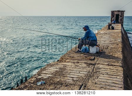 Tel Aviv Israel - October 18 2015. Angler fishes in Tel Aviv Port area