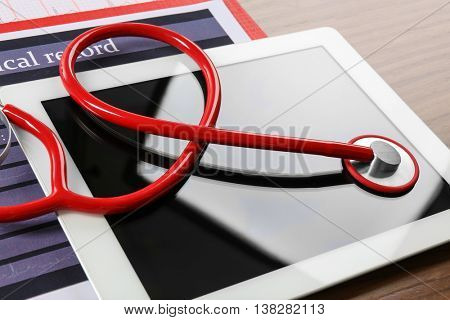 Medical concept. Medical stethoscope and tablet on wooden background