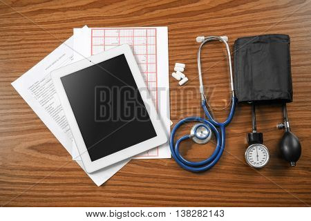 Medical concept. Medical manometer, tablet and a stethoscope on a wooden background