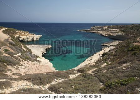 View down onto the small and secluded Delimara pool in the south of Malta showing the rocky surrounding coast and ocean.