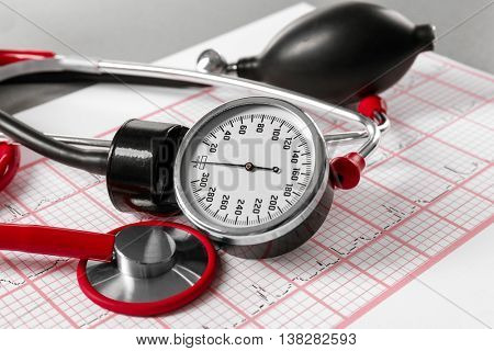 Medical concept. Medical manometer and a stethoscope on a cardiogram
