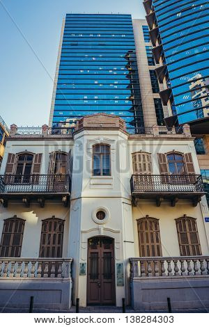 Tel Aviv Israel - October 21 2015. Main facade of renovated building called Mani House with modern office skyscraper on background
