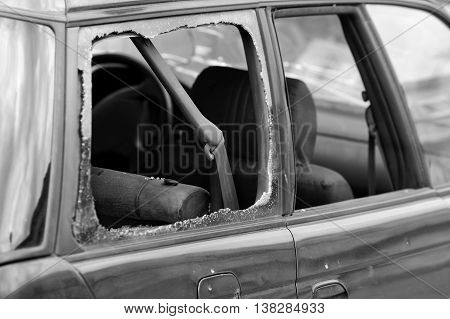 A car window smashed particular focus on the seat belt concept of safety on the roads. In black and white