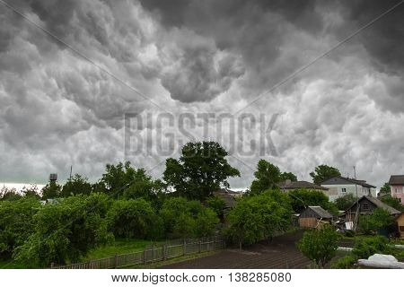 Village under heavy clouds in stormy weather before the rain