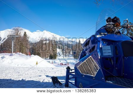 blue snowmobile on the background of snowy mountains and ski resort
