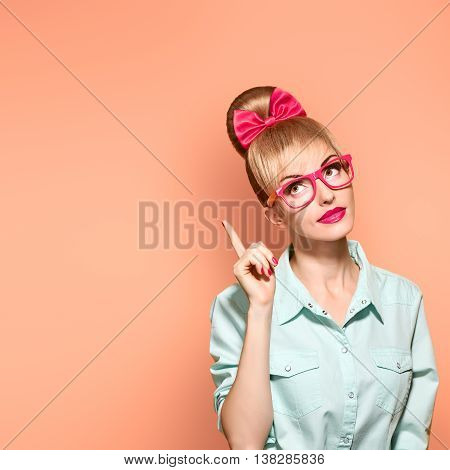 Fashion. Nerd woman in Stylish Glasses Having Fun. Hipster fashion girl think, idea. Playful Blonde with Glamour Pinup hairstyle, Trendy fashion Outfit, red bow Makeup. Unusual Creative, on yellow
