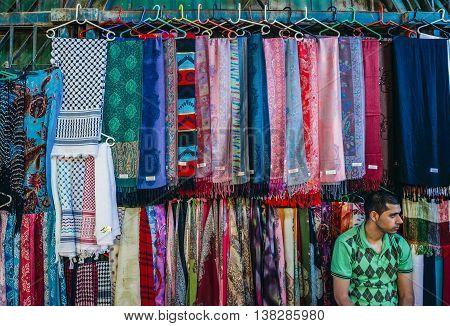 Jerusalem Israel - October 22 2015. Man sells textiles on Arab baazar located inside the walls of the Old City of Jerusalem