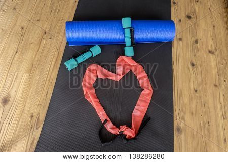 Collection of home exercise equipment on yoga mat on wooden floor background with resistance band forming a heart shape