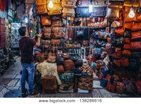 Jerusalem Israel - October 22 2015. Man sells leather products on Arab baazar located inside the walls of the Old City of Jerusalem