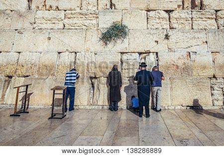 Jerusalem Israel - October 22 2015. People prays in front of ancient limestone wall known as Wailing Wall in the Old City of Jerusalem