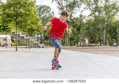 outdoor portrait of young smiling teenager boy riding short modern cruiser skateboard, urban background