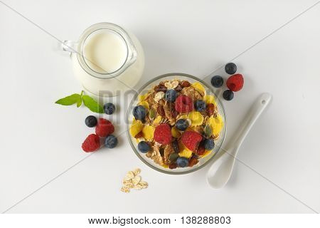 bowl of cereals and berry fruit with milk jug of milk on off-white background with shadows