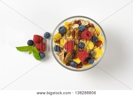 bowl of cereals and berry fruit on off-white background with shadows