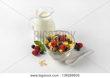 bowl of cereals and berry fruit with milk jug of milk