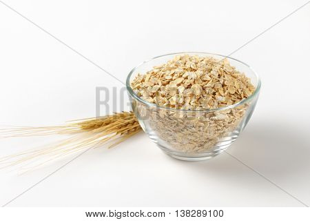 bowl of oat flakes on off-white background with shadows