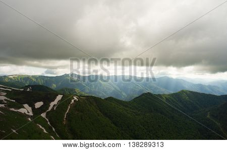 Mountain Landscape. The Road In The Mountains Covered By Forest. Light Rays Pierces Way Through The
