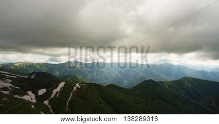 Mountain landscape. Light rays pierces way through the gloomy low clouds. Caucasus Mountains.