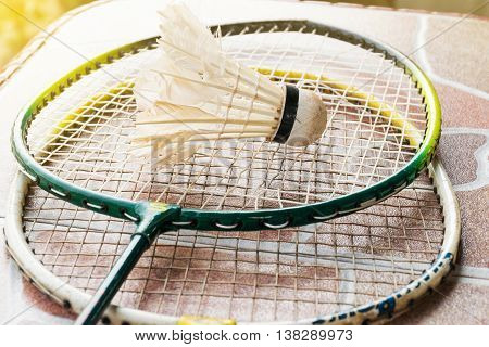 Old shuttlecock and badminton racket on the floor