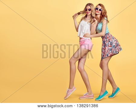 Fashion Hipster woman in Stylish Summer Outfit Having fun. Hipster sisters friends crazy cheeky emotions.Girl in Fashion sunglasses, Glamour hairstyle posing on yellow.Unusual Creative