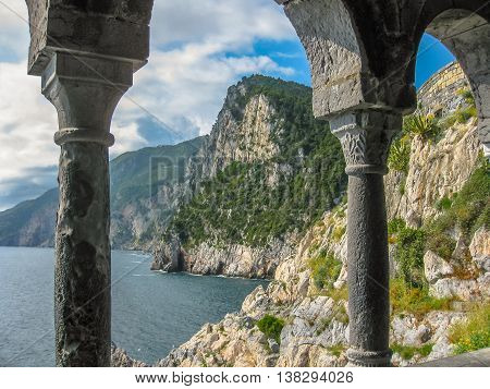 Beautiful shoreline scenery of Cinque Terre view from the columns of famous gothic Church of St. Peter, Chiesa di San Pietro, in the town of Porto Venere, Ligurian Coast, La Spezia, Italy.