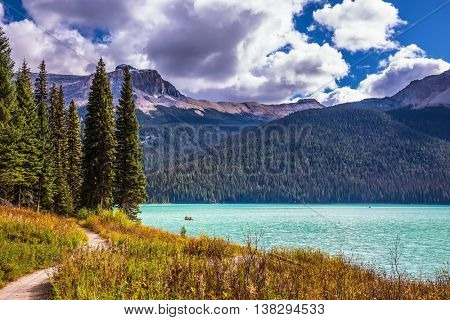 The Emerald Lake surrounded by coniferous forest  in the Rocky Mountains of Canada. Group of tourists crosses the lake in a rowboat