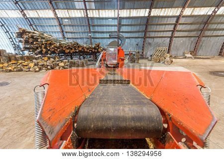 Machine for chopping firewood. Firewood processor in big warehouse.