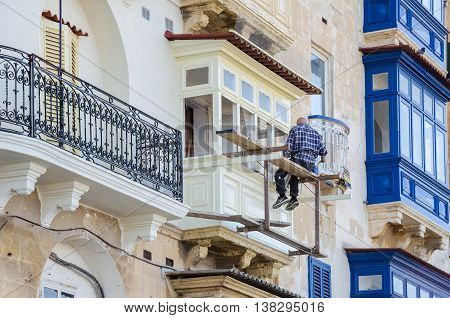 Valletta Malta - November 8 2015: Balconies in Valletta. Man painting his balcony.