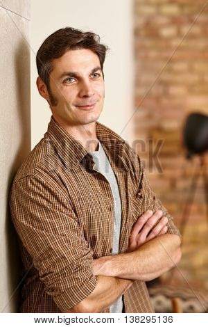 Casual man leaning against wall, smiling arms crossed, looking away.